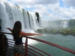 a tourist in front of iguazu falls