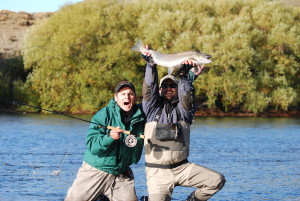 Two fishermen with a fish caught in Patagonia Argentina